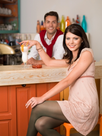 young beautiful caucasian girl sitting at a bar drinking a cocktail an smoking a cigarette with a guy behind the counter