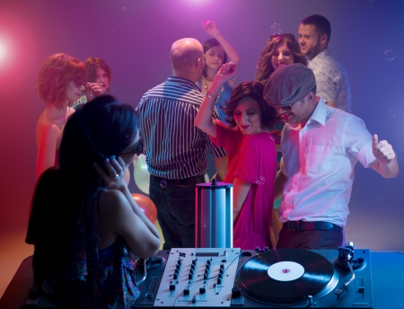 dancing club: young couple dancing together at a party with a female dj playing music with turntables, with other happy people in background and colorful lights