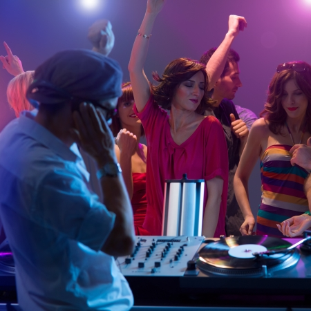 male dj playing music with turntables and headphones at a party with dacing people with their hands up and colorful lights photo