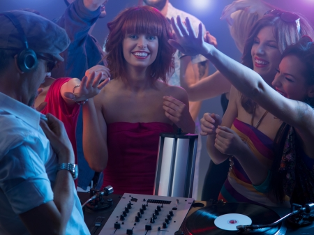 close-up of young attractive caucasian girl smiling at party in front of the dj that is playing music, with other girls around her reaching their hands towards the dj Stock Photo - 17753106