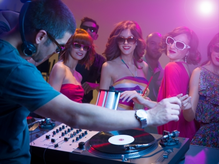 male dj playing music with turntables and headphones at a party with dacing people in front of him wearing sunglasses, with other people in background and colorful lights photo
