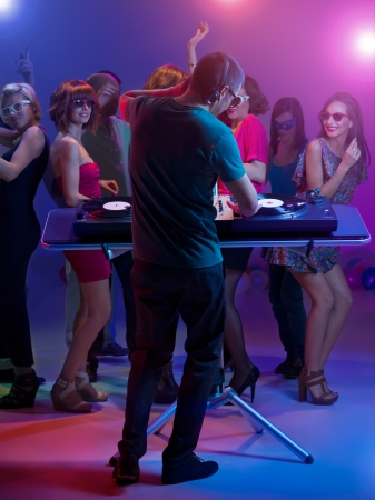 dj standing and playing music with turntables at a party with colorful lights and happy young dancing people wearing sunglasses Stock Photo - 17753133