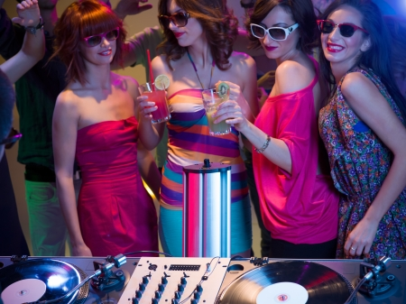 close-up of young attractive caucasian girls dancing and having fun at a party with sunglasses and cocktails in their hands, in front of dj mixing stand photo