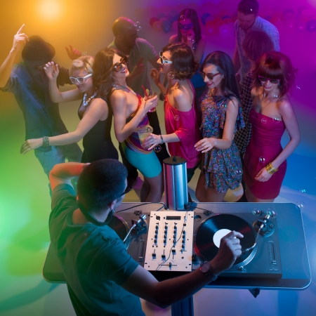 dance party: upper view of dj standing and playing music with turntables at a party with colorful lights and happy young people dancing with sunglasses and soap bubbles Stock Photo