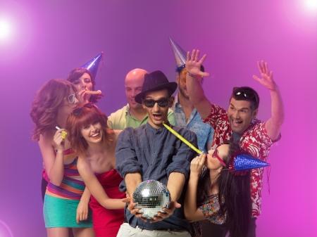 funny birthday: young handsome caucasian man holding a disco ball in his hands and looking at it amazed, with other happy people around him with party horns and hats Stock Photo