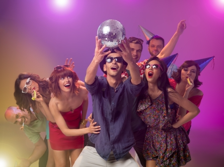 young handsome caucasian man holding a disco ball in his hands and looking at it amazed, with other happy people around him with party horns and hats, with colorfu lights in background Stock Photo - 17753116