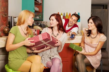 generoso: close-up de jóvenes muchachas atractivas caucásico sentados en el mostrador de una cafetería intercambio de regalos, con un chico guapo detrás de la barra que sostiene un anillo de compromiso en una caja Foto de archivo