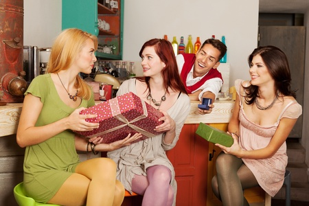 generous: close-up of young attractive caucasian girls sitting against the counter in a cafe exchanging presents, with a handsome guy behind the counter holding an engagement ring in a box Stock Photo