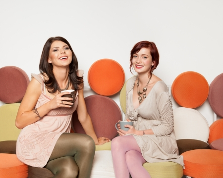 two young attractive caucasian girls sitting on colorful sofa with coffee mugs in their hands, having a great time photo
