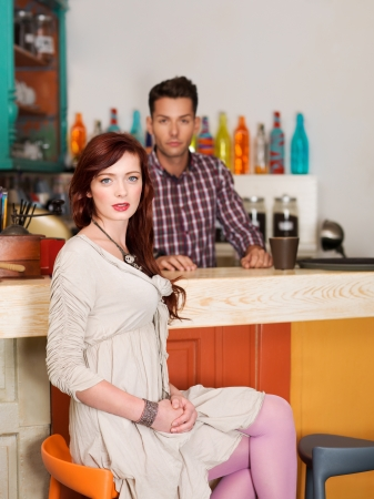 beautiful caucasian red haired girl sitting on a chair at the bar in colorful cafe with a barteneder behid the counter photo