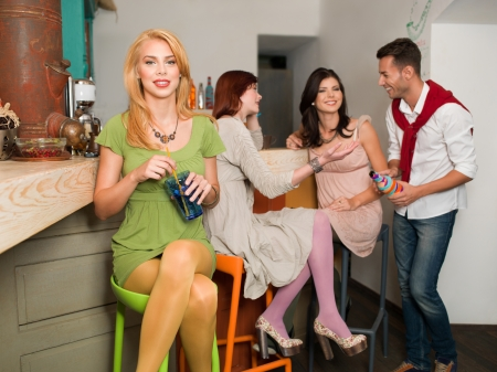young caucasian happy people in colorful cafe sitting at the counter drinking and socializing photo