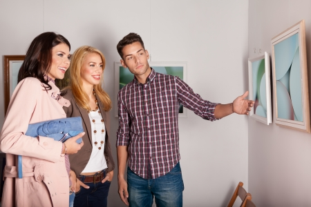 gallery interior: close-up of three young good looking people at an indoor  photography exhibition looking at a framed work and smiling, the young guy pointing at one of the photos