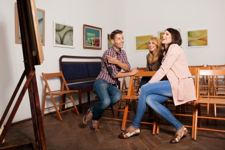 young good looking people at a photography exhibition sitting down on wooden chairs, laughing and pointig towards an art work photo