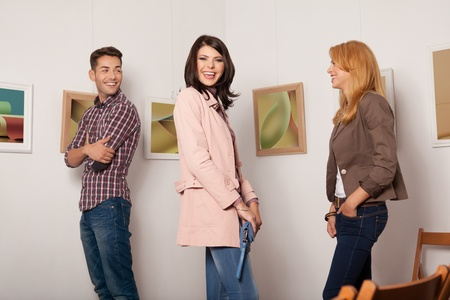 attractive young people standing at a photography exhibition laughing and enjoying themselves photo