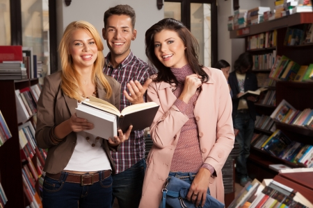 three young good looking people in a bookshop smiling, one of them holding an opened book in her hands Stock Photo - 17753032