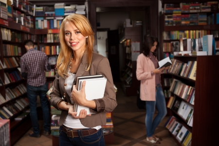 bookshop: close-up of young attractive caucasian girl in bookshop holding two different colored books in her hands with other people reading books in background