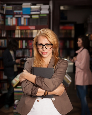 geeky: close-up of young attractive caucasian girl with geeky eyeglasses holding a book in her arms with bookshelves and other people in background Stock Photo