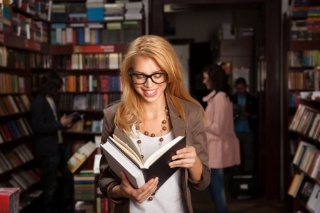 bookstore: close-up of attractive young girl with geeky eyeglasses in bookshop reading something from a book and laughing, ith other people and booksheles in background Stock Photo