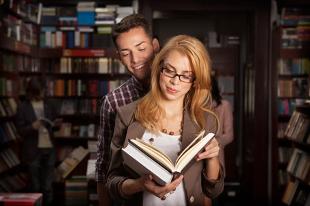bookshop: close-up of attractive young couple in a library reading a book together with other people and bookshelves in background