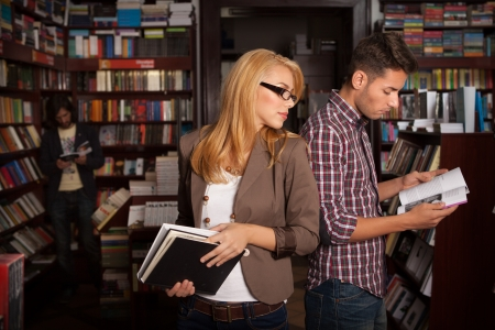 two caucasian young people standing back to back in a bookshop with books in their hands with other bookshelves in the background photo