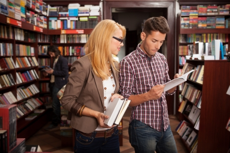 bookshop: two caucasian young people in a bookstore reading something in a book with many bookshelves in the background