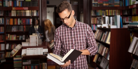 close-up of young caucasian man with eyeglasses in a bookstore with an opened book in his hands reading something with other bookshelves in background Stock Photo