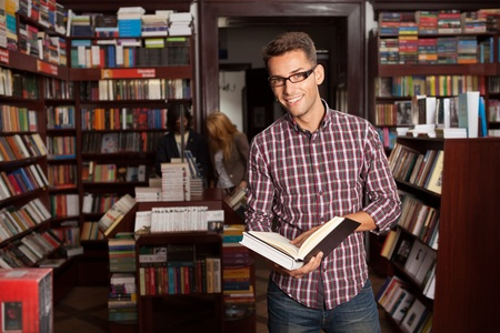 close-up of young caucasian man with eyeglasses in a bookstore with an opened book in his hands smiling, with other bookshelves in background Stock Photo