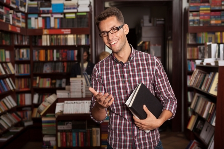 man holding book: close-up of young caucasian handsome guy with eyeglasses and book in his hands, in a bookstore