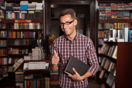 bookshop: close-up of young handsome caucasian guy with eyeglasses and books in his hand in a bookshop, thumbs up Stock Photo