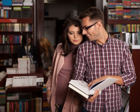 close-up of young caucasian couple in bookstore reading and pointing something in an opened book photo