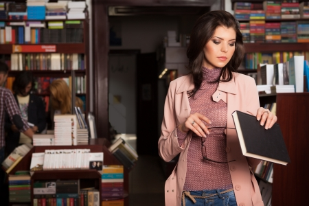 close-up of young attractive caucasian brunette girl in book store elegantly holding i her hands a pair of eyeglasses and a book reading the cover of it photo