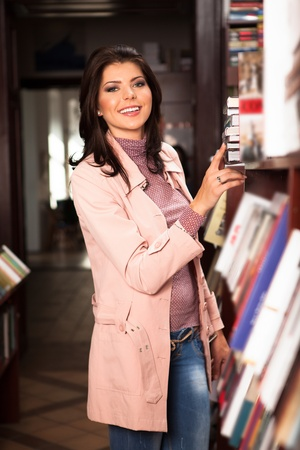 young attractive caucasian girl between the book shelves of a bookstore choosing something to read photo