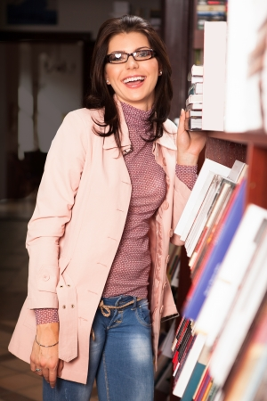 many hands: attractive caucasian woman with eyeglasses in a bookstore standing near a shelf with books, laughing
