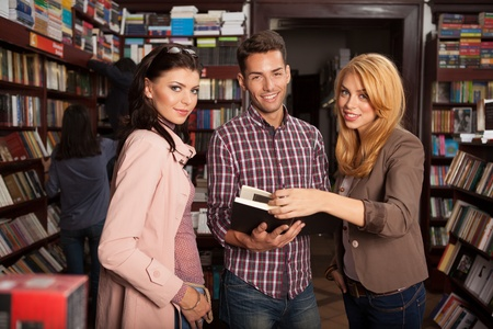 flipping: close-up of three young good looking people in a bookstore turning the pages of a book, smiling
