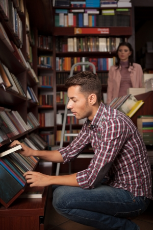 bookstore: close-up of young caucasian handsome guy in bookstore choosing a book from a lower shelf