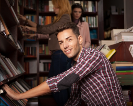 close-up of young handsome caucasian guy in a bookstore choosing a book from a shelf photo