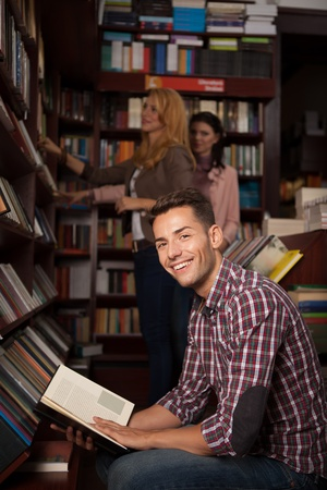 young caucasian handsome guy in a bookstore smiling with an opened book in his hands, with other people in background photo