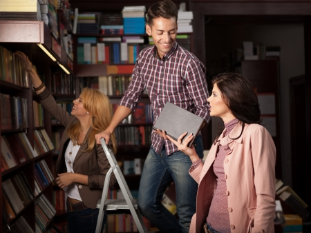 young caucasian guy up on a ladder in a library taking a book from an attractive girl, with another young girl in background choosing a book from a shelf photo