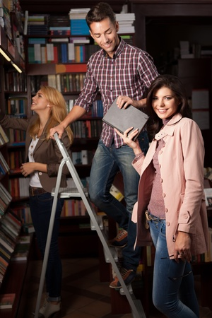 young caucasian guy up on a ladder in a library taking a book from an attractive girl, with another young girl in background choosing a book from a shelf Stock Photo - 17753105