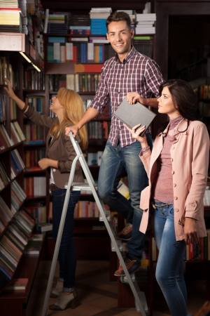 young caucasian guy up on a ladder in a library taking a book from an attractive girl, with another young girl in background choosing a book from a shelf Stock Photo - 17753090