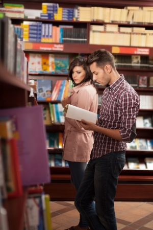 bookshop: young handsome caucasian guy in bookshop reading something in a book with a girl near him spying on what hes reading