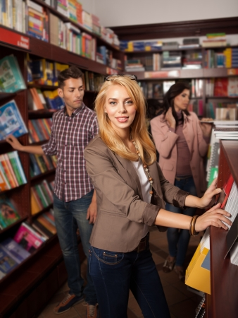 young beautiful caucasian blonde girl standing in a bookshop in front of a shelf with other people in background photo