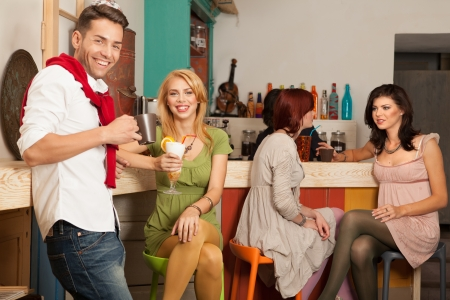young caucasian people in colorful cafe sitting and socializing, with other young girls sitting at the bar chatting photo