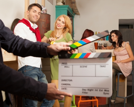 cinema scene in colorful cafe with young attractive caucasian people with movie clapper board in front of the frame Stok Fotoğraf