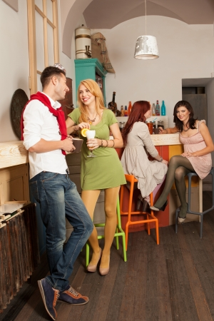 young handsome guy courting a young blonde girl in colorful cafe with other two young girls sitting at the bar having a conversation photo