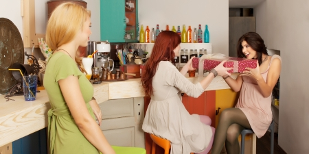 two young caucasian girls exchanging gifts sitting at the bar in a colorful cafe, with another girl watching them from behind photo