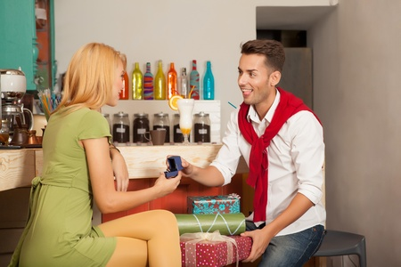 young handsome guy asking his girlfriends hand in marriage in colorful cafe with gift boxes photo