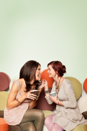attractive couch: two young beautiful caucasian girls sitting on colorful sofa with coffee mugs in their hands, laughing