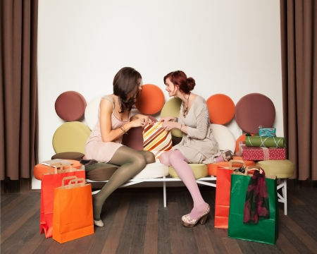 two young beautiful caucasian girls sitting on a colorful sofa with shopping bags and gift boxes around them looking with curiousity in a bag and laughing photo