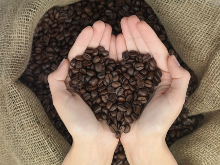 coffee heart shape held in hands over a canvas bag photo